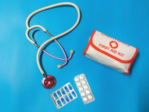 Blue background with a portable first aid kit, stethoscope and some medication in blister pack