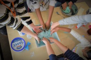 An overhead photograph of many hands reaching in to a big bowl full of light blue coloured slime.